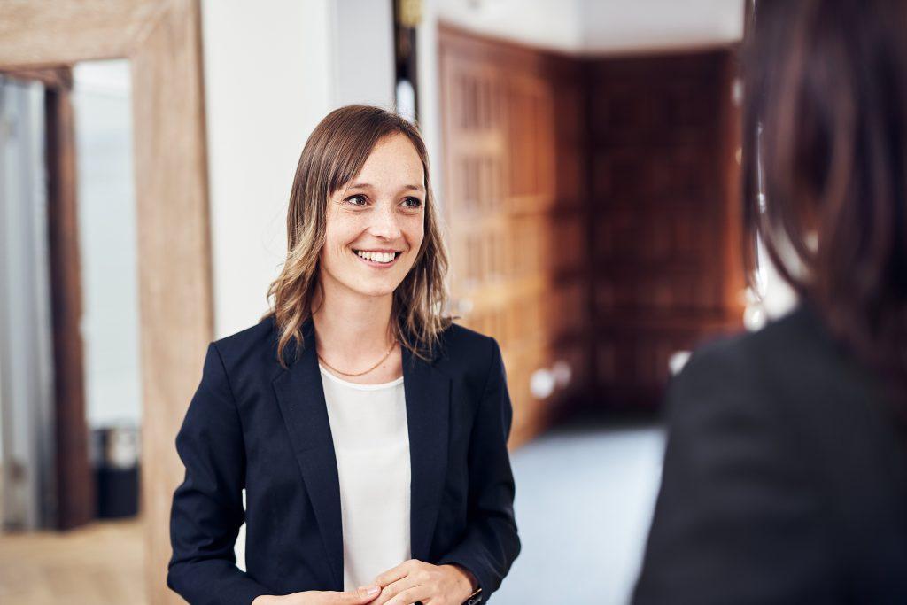 Eine junge Frau steht vor einem Raum und befindet sich in einer Gesprächssituation mit einer weiteren Frau, von der nur ein Teil von hinten zu sehen ist. Die junge Frau lächelt freundlich.