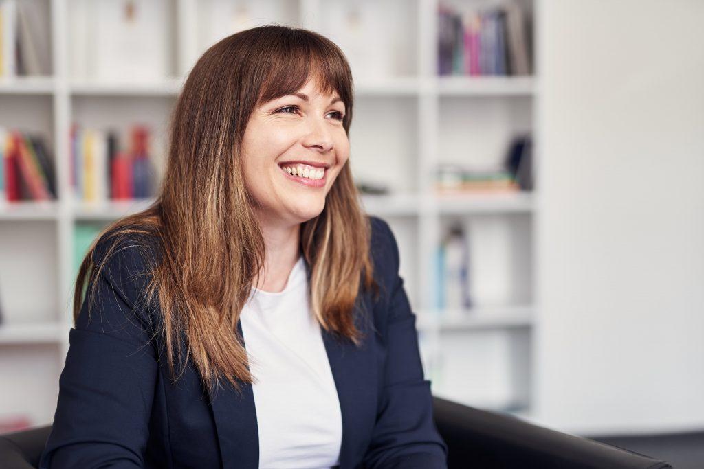 Eine Frau sitzt lachend auf einem Sessel und blickt zum rechten Bildrand.