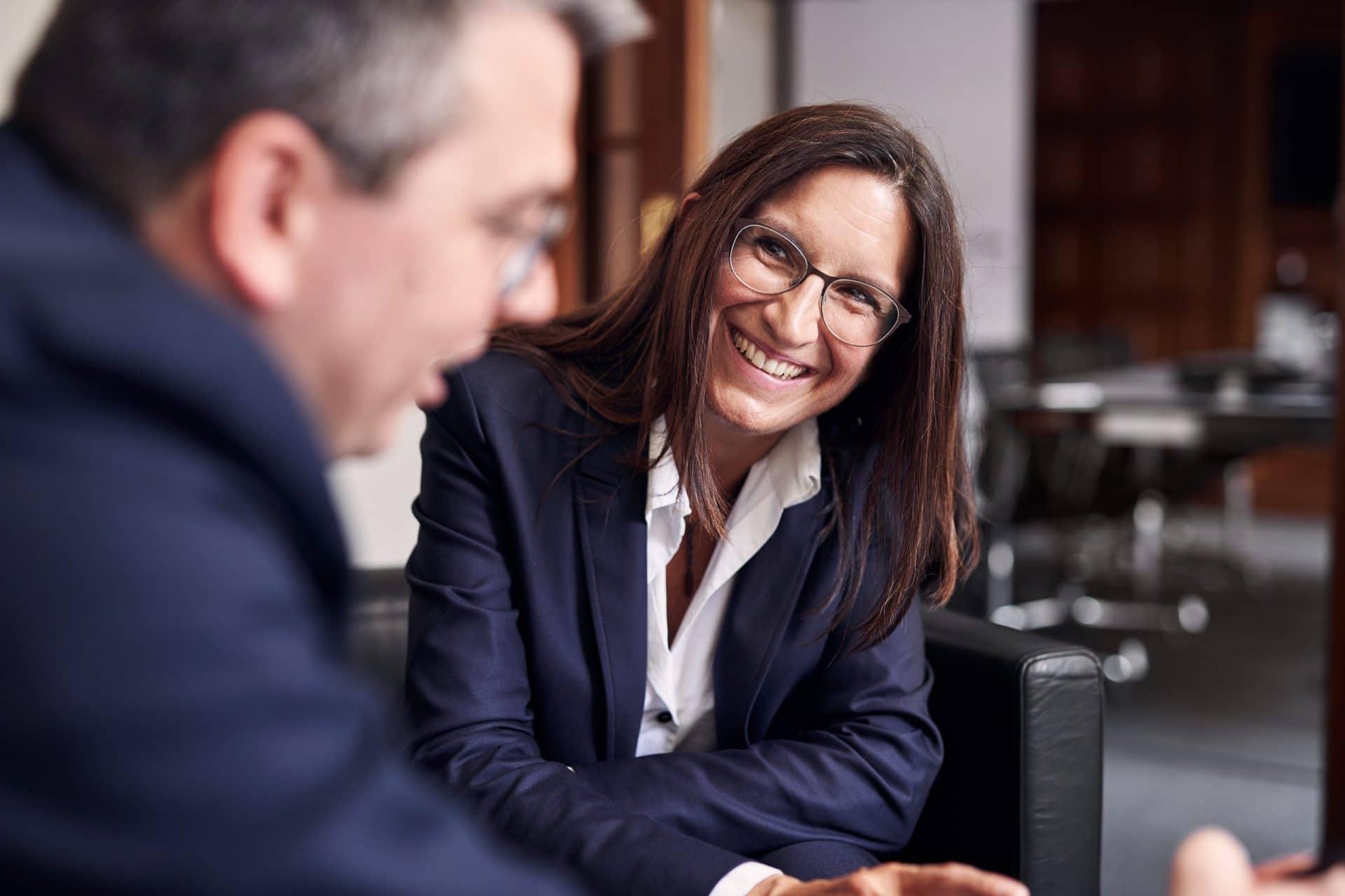 Eine Frau und ein Mann sitzen nach vorne gebeugt auf Sesseln. Der Mann blickt vor sich nach unten auf sein Mobiltelefon und die Frau lacht freundlich in seine Richtung.