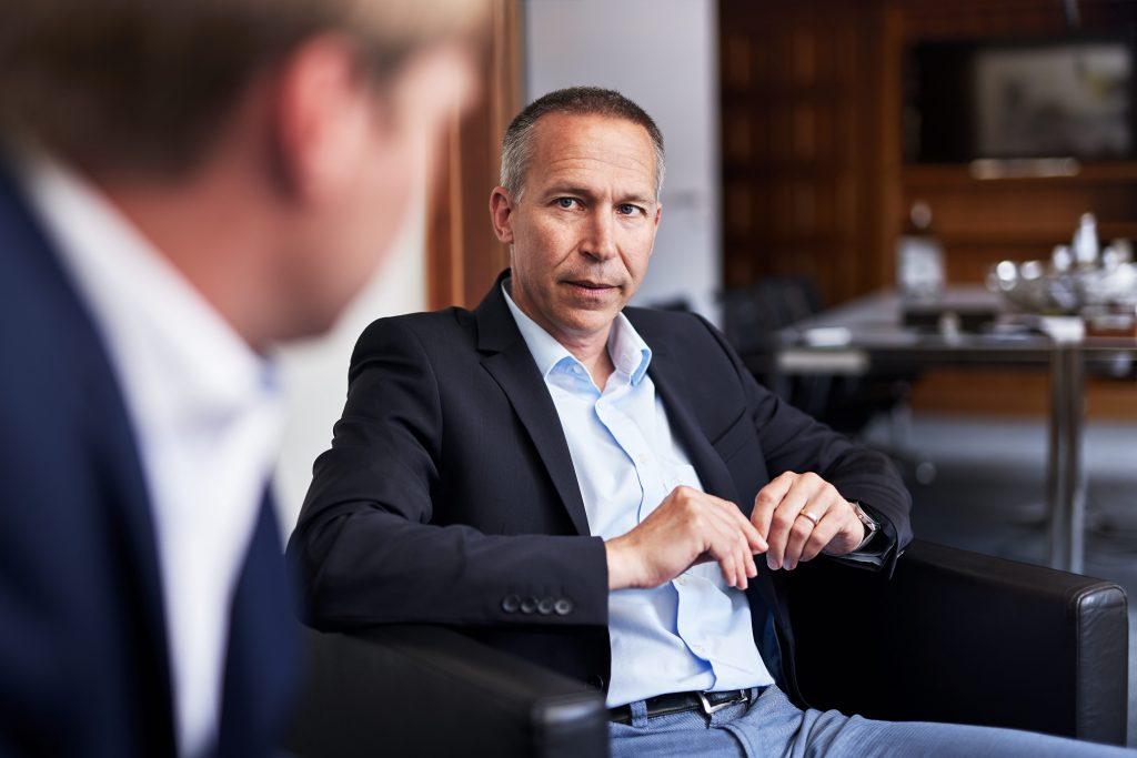 Ein Mann sitzt zurückgelehnt und hört konzentriert einem anderen Mann zu
