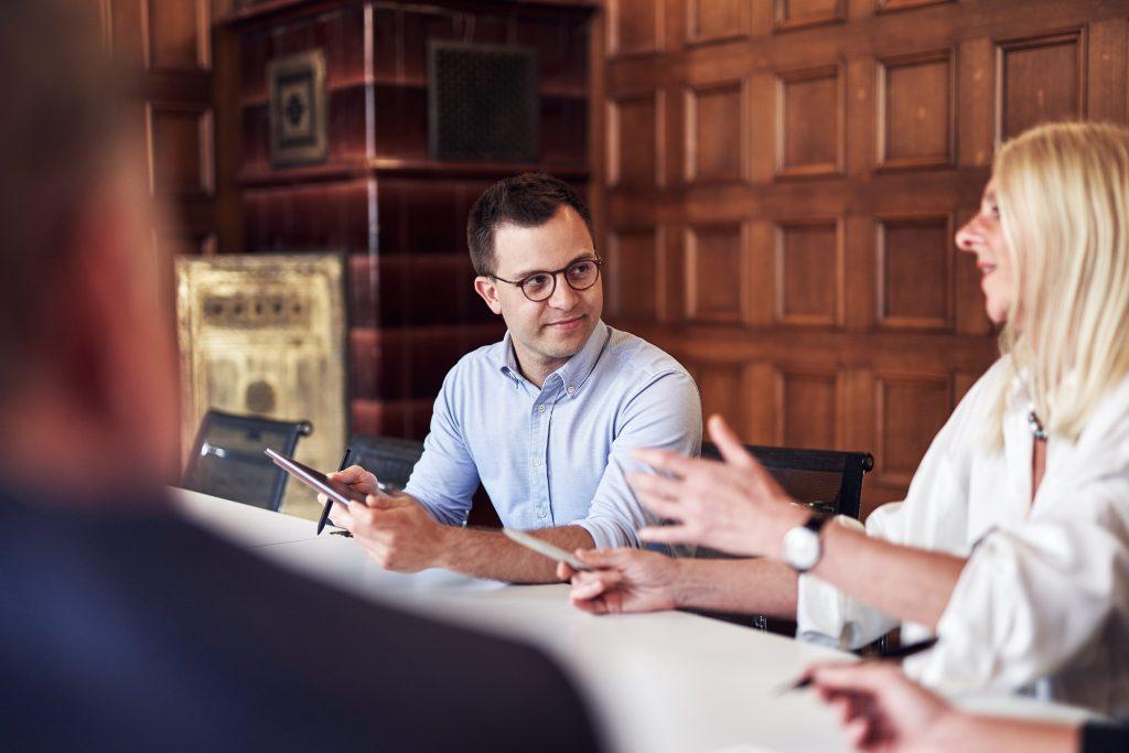 Drei Personen sitzen am Tisch. Eine Frau erklärt und gestikuliert, die beiden Männer hören zu.