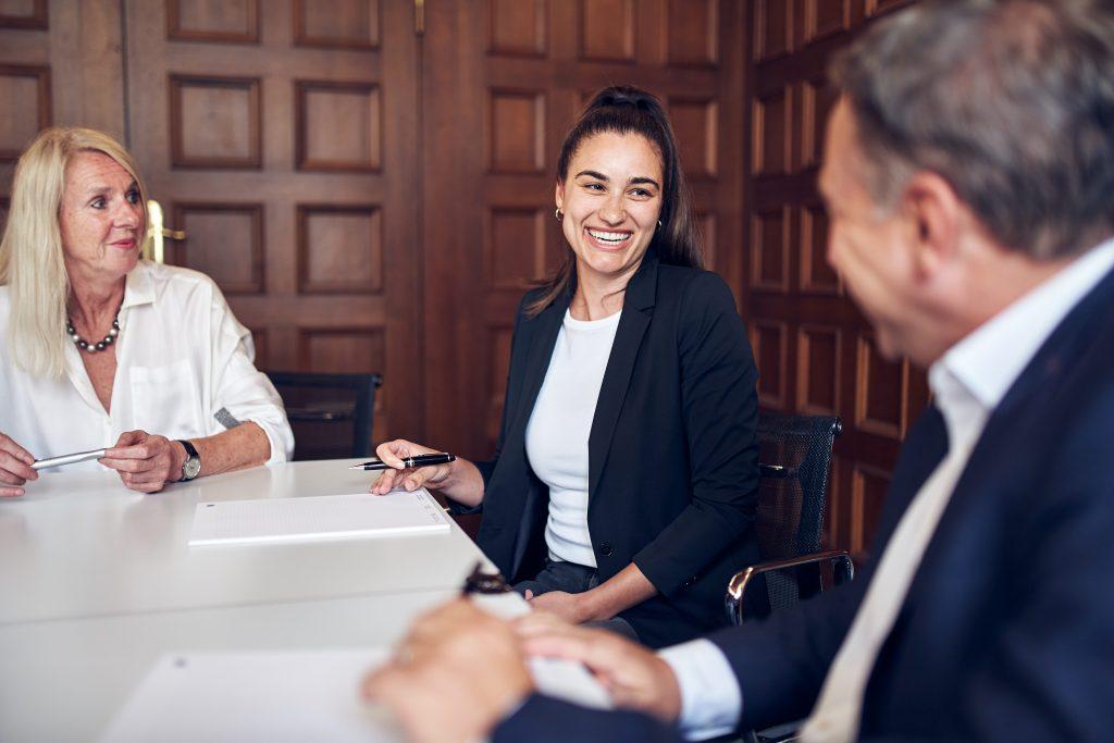 Zwei Frauen und ein Mann sitzen am Tisch. Eine Frau und der Mann lachen herzlich.
