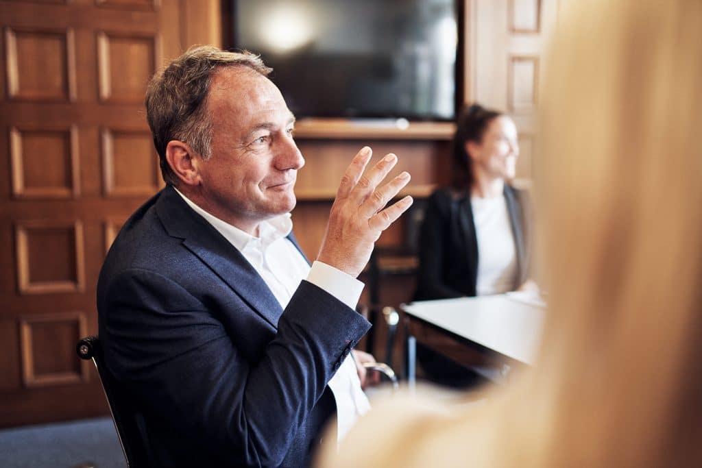 Ein Mann und eine Frau sitzen am Tisch und blicken zum rechten Bildrand. Der Mann gestikuliert mit einer Hand. Am rechten Bildrand sieht man den Kopf einer Frau von hinten.