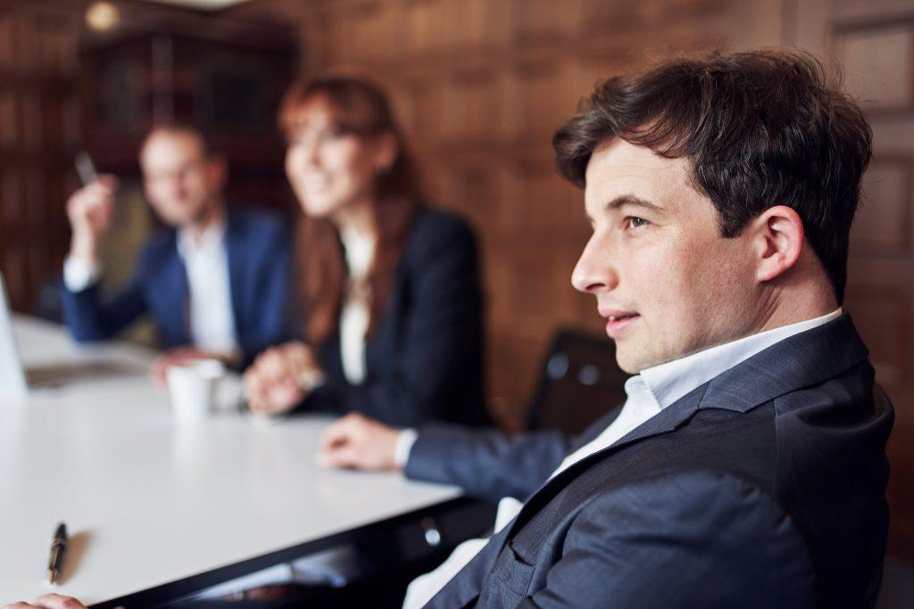Eine Frau und zwei Männer sitzen am Tisch und schauen konzentriert und aufmerksam nach links.