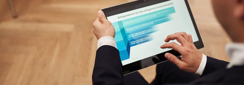 """Ein Tablet-Computer zeigt eine Präsentationsfolie mit der Überschrift """"Erfolgsfaktoren für eine erfolgreiche Zusammenarbeit""""."""